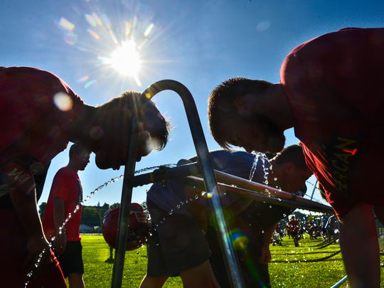Milaca football players take a water break during a hot morning of practice Wednesday, Aug. 17, at Milaca High School.