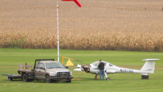 A plane receives repairs at Maple Grove Airport just off the runway.