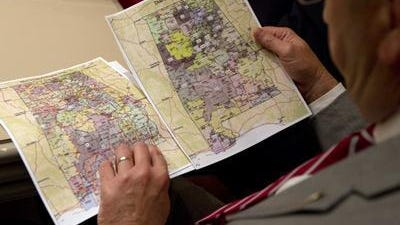 A legislator reviews proposed redistricting maps in May 2012. Three federal judges are scheduled to hear arguments Tuesday over whether the maps were constitutional.