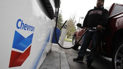 In this Jan. 28, 2011 file photo, a customer pumps gas at a Chevron gas station in Mountain View, Calif. Chevron Corp. says its net income fell 27 percent in the first quarter because of lower global oil prices and decreased production of oil as a result of bad weather.