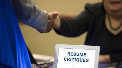 A job seeker stops at a table offering resume critiques during a job fair held in Atlanta. The Labor Department reports the number of people seeking U.S. unemployment benefits last week rose 2,000 to a seasonally adjusted 304,000. Jobless claims continue to be near pre-recession levels despite the slight increase.