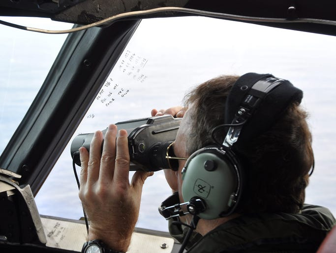 A crew member aboard a Royal New Zealand Air Force P3 Orion aircraft searches for debris from the missing Malaysia Airlines jet on April 2 over the Indian Ocean northwest of Perth, Australia. The Boeing 777 airliner with 239 people on board disappeared on March 8 on a flight from Kuala Lumpur to Beijing.