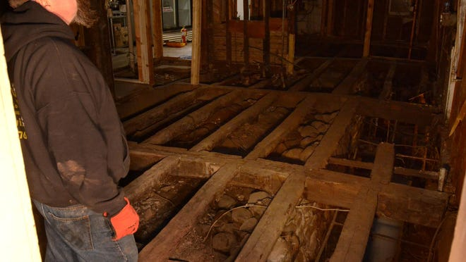 Chris Stone surveys the original support beams for the New Hudson Inn March 28 during its renovation. The inn was originally built in 1831 along a trail that would become Grand River Avenue. The beams in the original inn were cinched together with wooden dowels where the beams joined up.