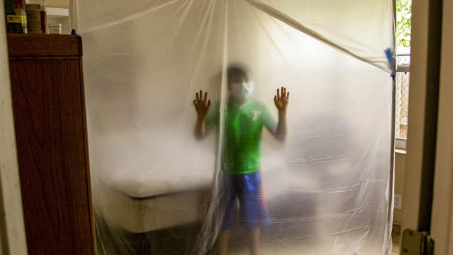 A child checks out a protective curtain installed in a Lake Worth home Monday as part of a sanitation kit to prevent the transmission of the Coronavirus. Lake Worth's Guatemalan-Maya Center is providing kits to families inflicted with the virus.