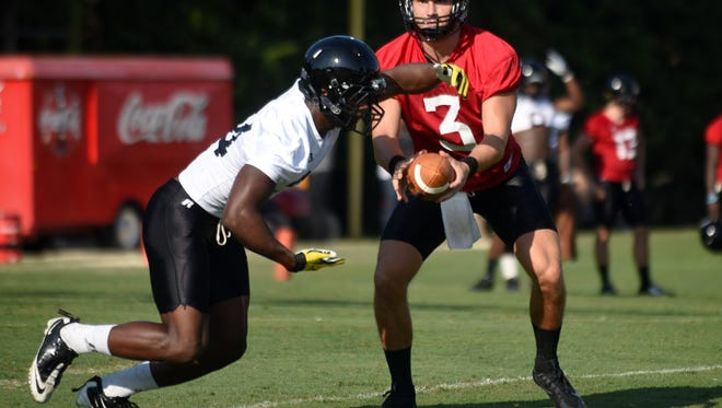 Southern Miss player Parker Adamson hands off the ball to George Payne at the first day of fall football camp on Friday.