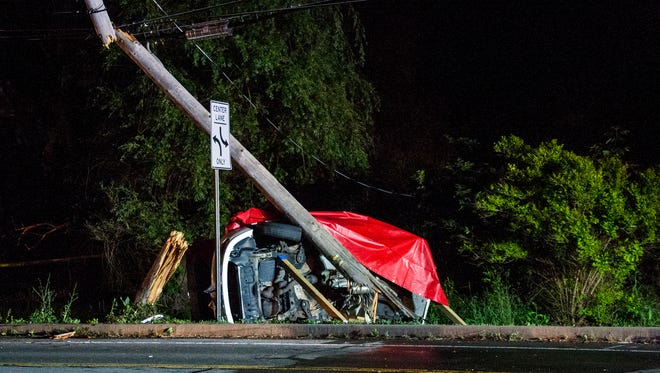 The car sheared the utility pole into three pieces before coming to rest on it's side.
