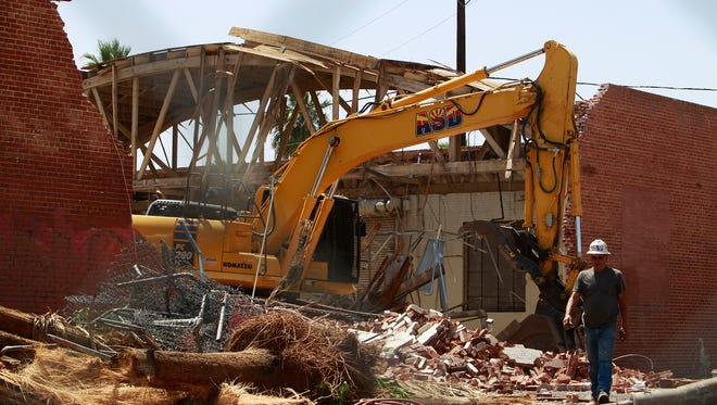 Part of the historic Circles building is demolished on Friday, April 15, 2016 in Phoenix. The building was once home to an auto-dealership and a record store.