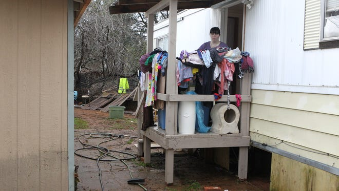 Jenny Pitman dries out clothes Monday after water flooded her home in Shasta Lake.