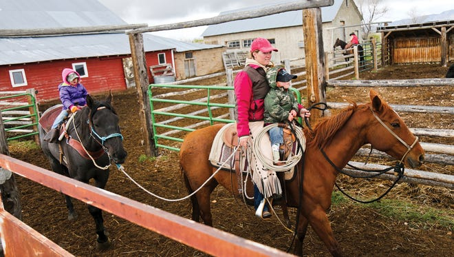 In this May 27, 2017, photo, Pennie Cowdell rides with her son Spade as her daughter Ravada follows behind at the Cow Camp Ranch outside of Laramie, Wyo.