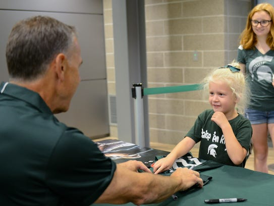 """Riley Orlowski, 6, of Mason, points out where she'd like MSU football coach Mark Dantonio to sign her Spartan football jersey during last year's """"Meet the Spartans"""" event at Spartan Stadium."""