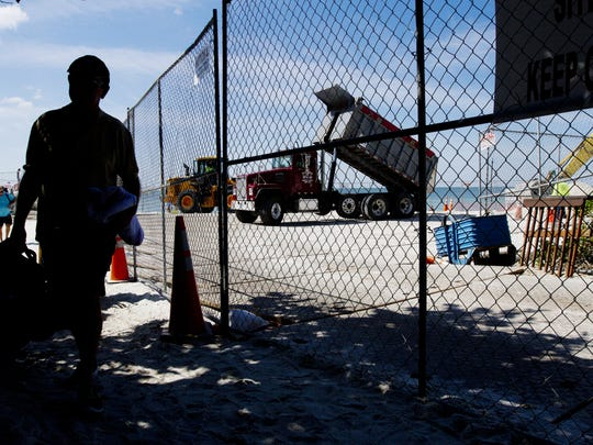 A dump truck carrying sand from Stewart Mining in Immokalee dumps its load on Vanderbilt Beach in Naples on Monday. A beach renourishment project is underway. The project should last through February according to Collier County Officials.