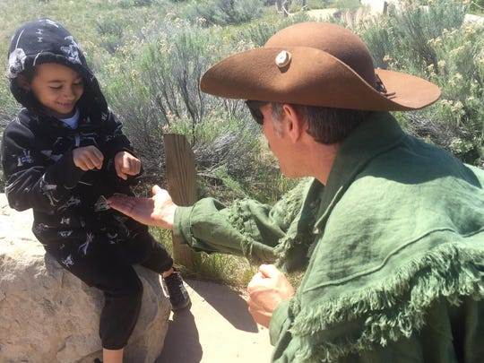 """Duane Buchi teaches Hiro Sims, 6, a traditional Native game designed to each at """"poker face,"""" at the Lewis & Clark Interpretive Center on Sunday afternoon."""
