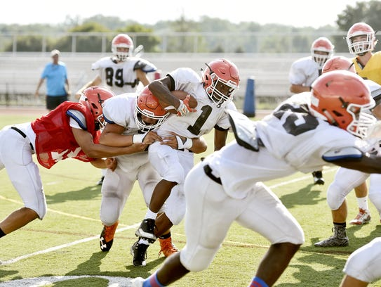 Central York's Noreaga Goff, center, carries the ball