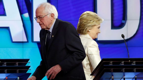 Bernie Sanders and Hillary Clinton pass each other at the start of a break during the CNN debate at the Brooklyn Navy Yard on April 14, 2016.