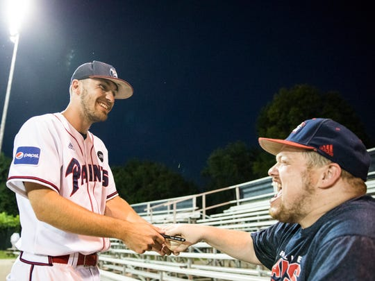 Infielder Chad Roberts signs a ball for Josh Zonner, who attends many of the Paints' home games, after a winning game against the Lafayette Aviators on June 11, 2018.