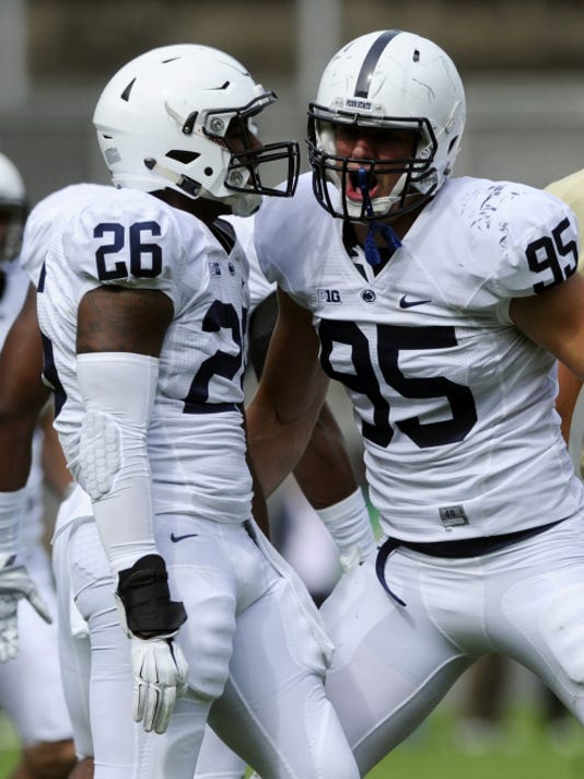 Penn State defensive lineman Carl Nassib, right, gets pumped up with linebacker Brandon Bell during a game last season. Nassib returns this season to the line that figures to be one of the Lions' strengths.