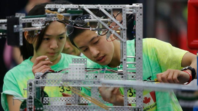 Cassandra Lam, right and Tim Chang, both of Winston Churchill High Schooll in Alberta, Calif., worked on their school's robot prior to the start of the VEX Worlds 2015 competition.