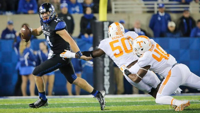 Kentucky quarterback Patrick Towles scrambles to get past Tennessee defensive linemen Corey Vereen (50), and Dimarya Mixon (40) during the first half Saturday in Lexington, Ky.