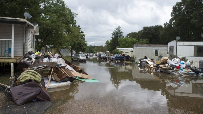 Piles of debris line the side of the roads in St. Helena Parish, La., recently as residents return to remove water damaged contents from their homes.