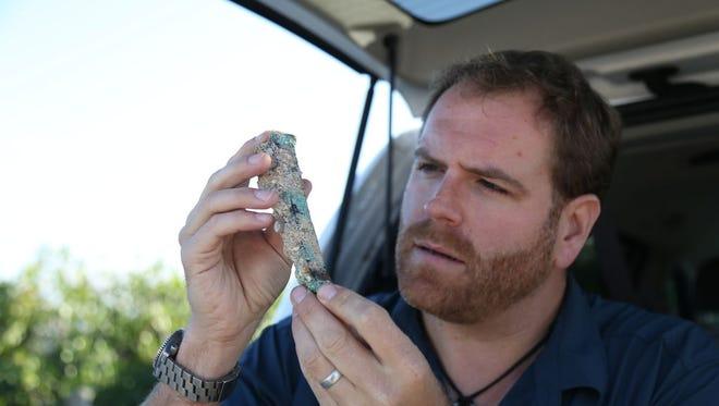 "Josh Gates examines a piece of treasure discovered off the Treasure Coast in ""Lost Spanish Fortune, Found!"""