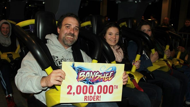 Phil Harding displays his sign proclaiming him as the Banshee's 2 millionth rider. The Banshee was the first coaster to deliver 2 million rides in a debut season since the Vortex did it in 1987.