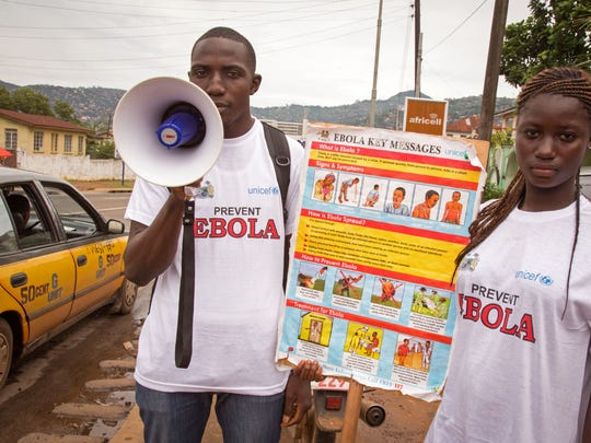 A man and woman taking part in a Ebola prevention campaign holds a placard with an Ebola prevention information message in the city of Freetown, Sierra Leone, Wednesday, Aug. 6, 2014. The World Health Organization has begun an emergency meeting on the Ebola crisis, and said at least 932 deaths in four African countries are blamed on the virus, with many hundreds more being treated in quarantine conditions. (AP Photo/ Michael Duff)