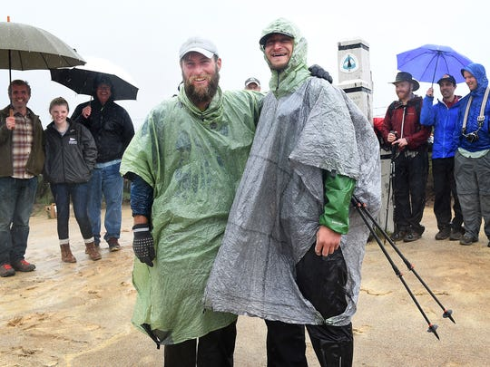 Winter time through hikers Justin Lichter and Shawn Forry pose for a portrait with their supporters after arriving at the southern terminus of their historic journey on the Pacific Crest Trail at the Mexican border near Campo, Calif. on March 1, 2015.