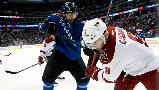Arizona Coyotes center Sam Gagner, front, battles for control of the puck in the corner with Colorado Avalanche defenseman Jan Hejda, of the Czech Republic, in the third period of an NHL hockey game Monday, Feb. 16, 2015, in Denver. Colorado won 5-2.
