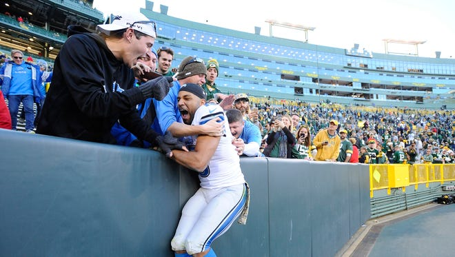 Lions wide receiver Golden Tate does the Lambeau Leap with a small group of Lions fans after Sunday's win in Green Bay.