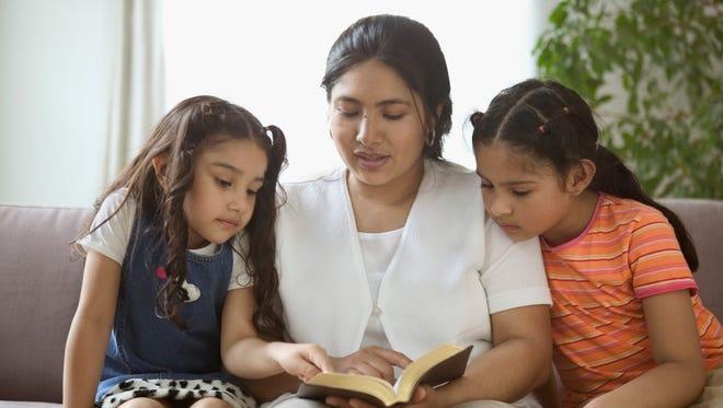 Una madre le lee a sus dos hijas.