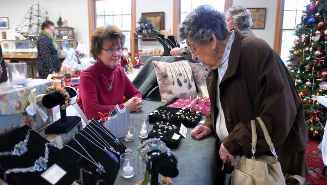 Vendor Elaine Schaefer, left, waits as Lea Mizdrak, of Capac, glances over Schaefer's jewelry, December 2011, during the Cranberry Christmas craft show at the Capac Historical Museum.