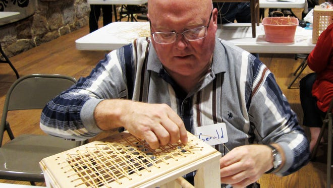 Gerald Clark of Hagerstown caned a top for a handcrafted foot stool in last year's caning workshop.