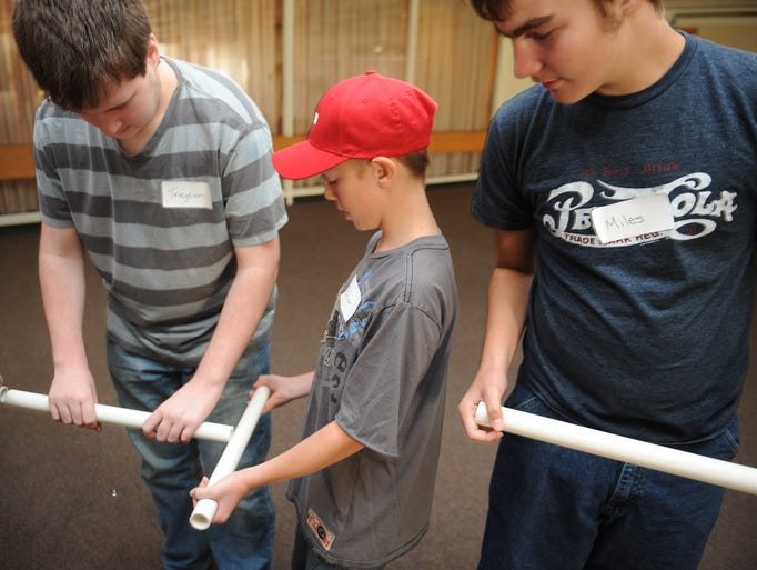 Briar Swigert, 11, blocks off a pipe holding a marble during a group activity at Howâ??s that Made Manufacturing Camp at the Coshocton County Career Center. The team was trying to carry a marble through several pipes and deliver it to a bowl on the other side of the room.