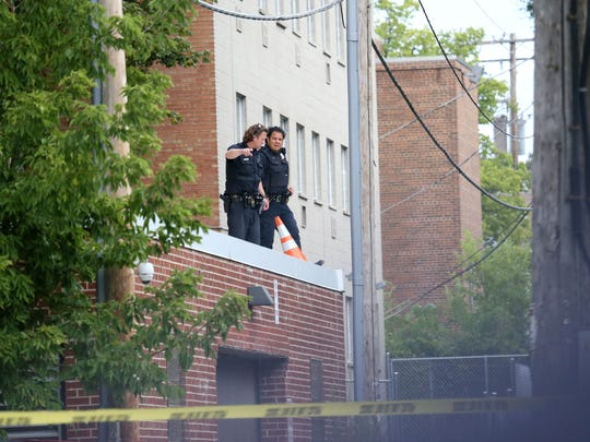 Milwaukee police search a roof area where witnesses say the shooting occurred near N. 29th St. and W. Wisconsin Ave.