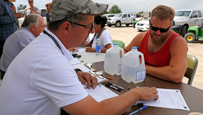 New Mexico Environment Department liquid water program manager Jim Vincent, helps a citizen fill out the proper paper work on Aug. 10 during water testing at San Juan County's Lee Acres Sheriff's Substation in Farmington.