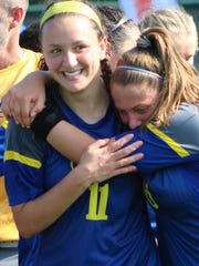 Senior Annie Bruce (left) is hugged by sophomore teammate Chloe Aberlarde after leading Marian to a second straight D-2 state soccer title Saturday in Williamston.