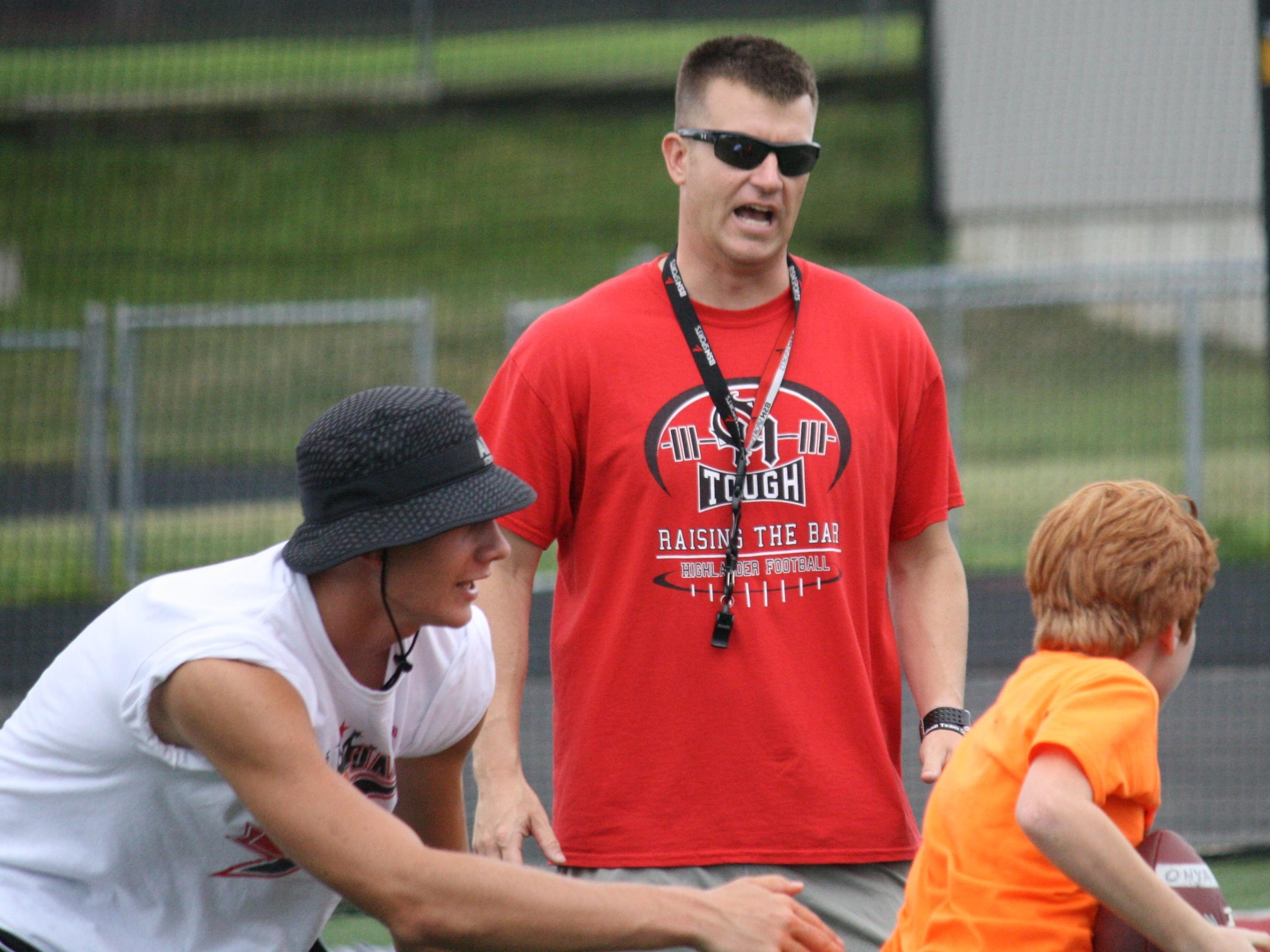 New Oak Hills football coach Evan Dreyer, middle, works during a youth football camp in June.