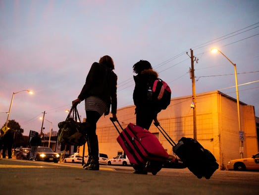 Travelers pull their luggage as they walk to a Greyhound
