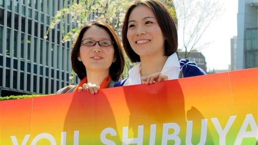 """Koyuki Higashi, right, and Hiroko Masuhara, a rare visible and vocal lesbian couple in Japan, smile with a rainbow banner reading: """"Thank you, Shibuya"""" in front of Shibuya ward office in Tokyo after Shibuya ward became the first locale in Japan to recognize same-sex partnerships as the """"equivalent of a marriage,"""" guaranteeing the identical rights of married couples with a landmark vote by the ward assembly on  Tuesday, March 31, 2015. The couple have been together for three years, and held a symbolic wedding at Tokyo DisneySea two years ago."""