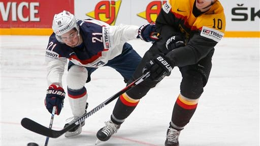 Dylan Larkin of the U.S, left, fights for the puck with Germany's Christian Ehrhoff during the Hockey World Championships Group B match in St.Petersburg, Russia, Sunday, May 15, 2016. (AP Photo/Dmitri Lovetsky)