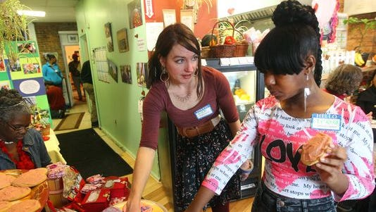Lisa Barker, left, assistant director at the Seedfolk Store, works with Ty'Reka Middleton, 15, during an open house.