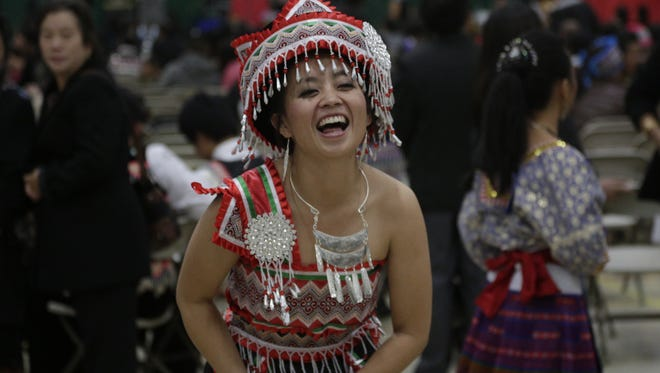 Michelle Lor of Wausau laughs as she plays the traditional ball-tossing game with a male partner at the Hmong New Year celebration at Greenheck Field House in Weston, Saturday, November 2, 2013.