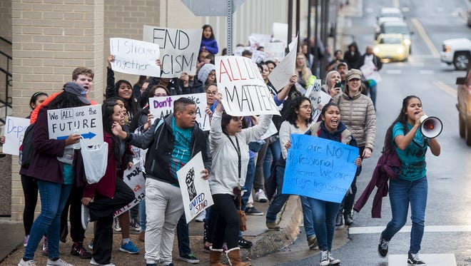 Harrisonburg High School students, joined by members of the community, cross the street into Court Square to stage a demonstration against President-elect Donald Trump in Harrisonburg, Va., on Nov. 14, 2016.