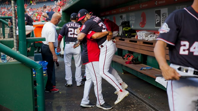 In this May 4, 2018, photo, Washington Nationals Bryce Harper is hugged and lifted off the ground by his manager Dave Martinez in the dugout prior to the start of a baseball game against the Philadelphia Phillies at Nationals Park in Washington. High fives and fist bumps are out. Hugs are a no-go. And just like crying, there's no spitting in baseball, at least for now. Things sure will be different when it's time to play ball in two weeks.