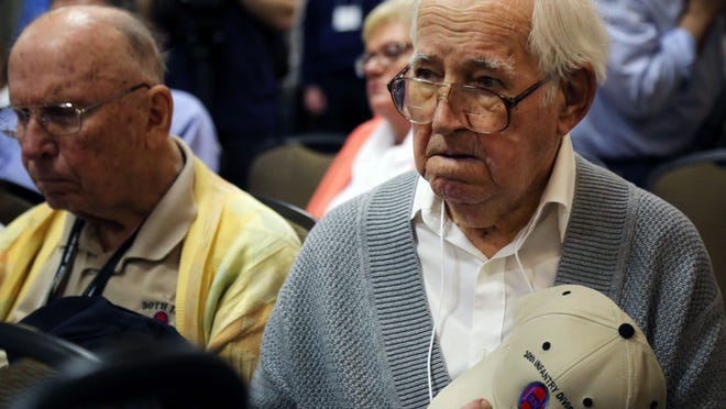"""World War II veteran Jack Kraus places his hat over his heart as """"Taps"""" is played in honor of the 30th Infantry Association members who passed away since their reunion last year."""