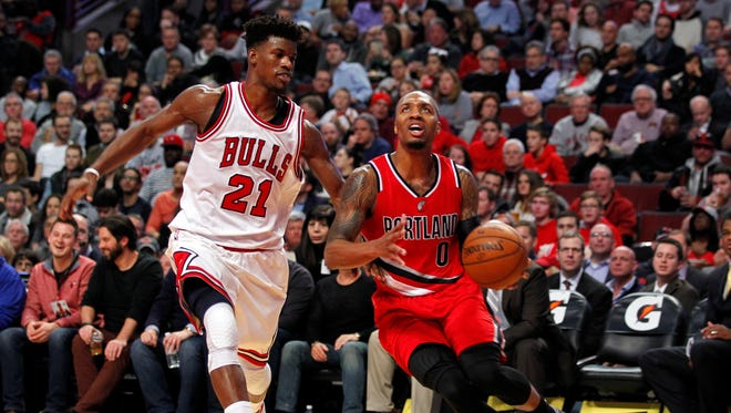 Portland Trail Blazers guard Damian Lillard (0) is defended by Chicago Bulls forward Jimmy Butler (21) during the third quarter of the game at United Center.