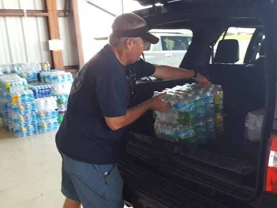 Mark Coomber of Stuart unloads his vehicle after making a donation at Stuart Jet Center for Bahamian families in need.