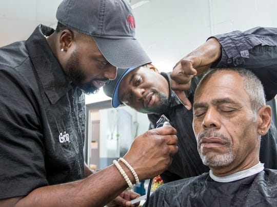 Owner Adrian Ace Wallace, center, gives a few pointers to Grip as he works on Lloyd West's hair cut at the Barber Academy in Pensacola on Thursday, December 28, 2017.