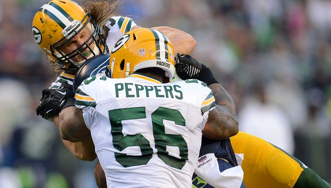Packers linebackers Clay Matthews and Julius Peppers tackle Seattle Seahawks quarterback Russell Wilson during their Week 1 game at CenturyLink Field in Seattle.