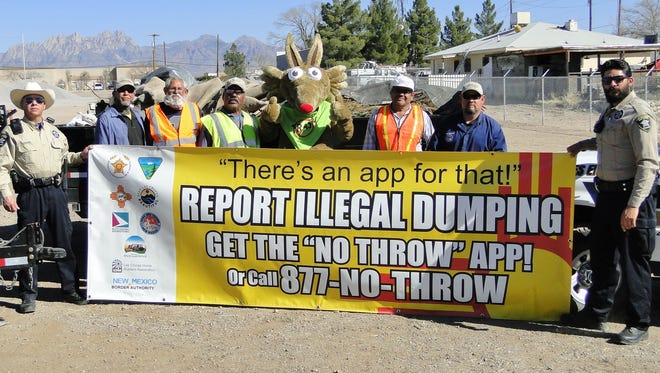The newly organized county illegal dumping cleanup crew, with mascot Carlos the Coyote and county Codes Enforcement officers.    PHOTO 2: Codes Enforcement Officers Kevin Apodaca and Robbie Acosta showing the Illegal Dumping Partnership sign that explains how to report and stop illegal dumping.